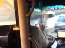 Buschauffeur stuurt met één hand ... om zijn rit te filmen
