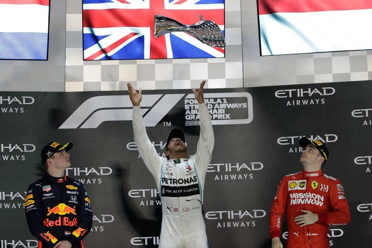 Lewis Hamilton gooit zijn prijs van de Grand Prix in Abu Dhabi de lucht in, links kijkt Max Verstappen toe. Beeld AP