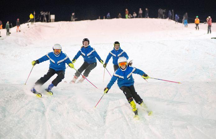 Leden van het wedstrijdteam op echte sneeuw op skibaan De Schans te Uden