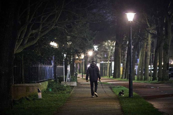 Een man laat zijn hond uit in Den Haag.