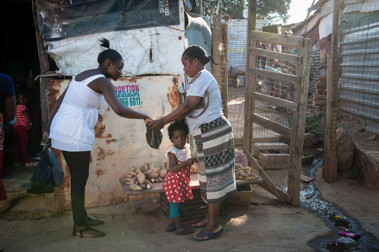 Een vrouw verkoopt wat aardappelen aan een klant in Zandspruit. Beeld Bram Lammers