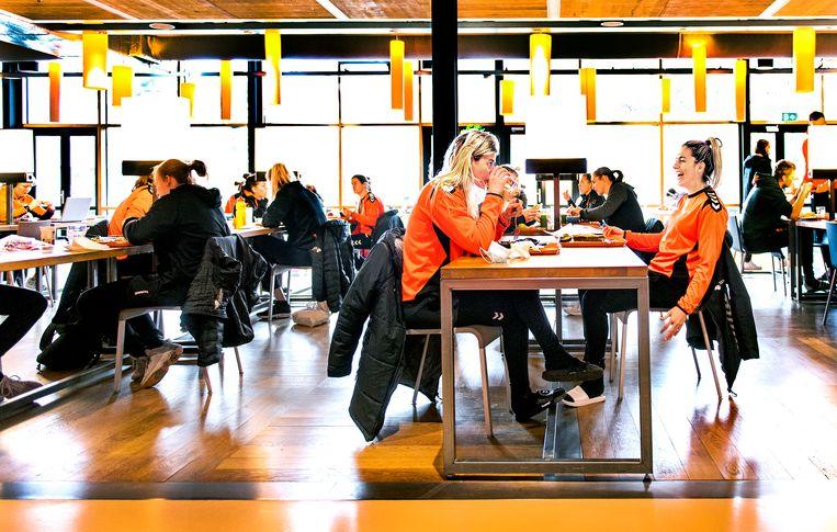 Handbalsters Estavana Polman (rechts) en Angela Malestein tijdens de lunch in het topsportrestaurant op Papendal. Polman scheurde in augustus 2020 haar kruisband in de rechterknie en is net weer aangesloten bij de nationale handbalselectie. Zij hoopt deze maand haar rentree te maken tegen Kroatië. Nog 109 dagen tot Tokio. Beeld Klaas Jan van der Weij / de Volkskrant