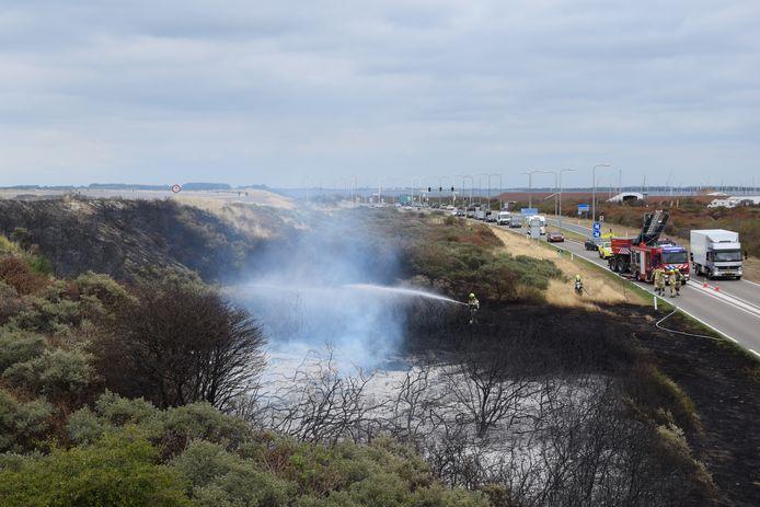 De brandweer blust de duinbrand bij de N57