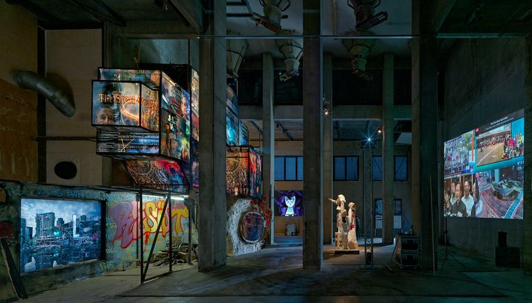 De toon van de tentoonstelling wordt gezet door een installatie van Rob Voerman, een grot die bekroond wordt door een Times Square-achtig verlichte toren met billboards. Beeld Gert Jan van Rooij