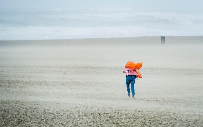 Een wandelaar trotseert het strand van Scheveningen tijdens een officiële zomerstorm in 2015.