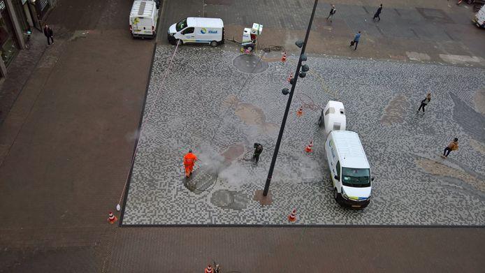 Schoonmakers spuiten de vervuilde mozaïekvloer op het Vredenburgplein schoon.