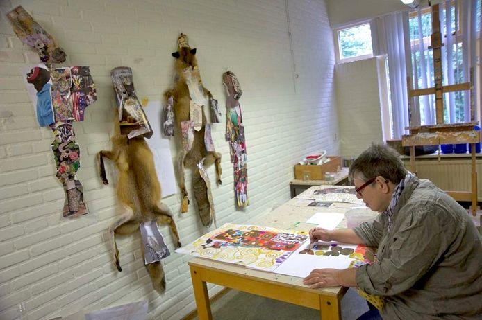 Ria Mul aan het werk op het atelier van Artenzo, met door Marc Mulders verzamelde beelden als 'voeding' aan de muur.