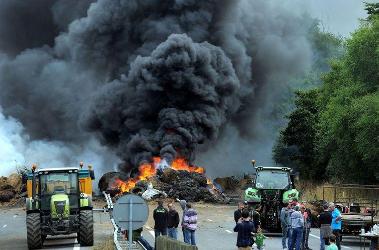 Op de weg tussen Morlaix and Brest staken boze boeren autobanden in brand. Beeld afp