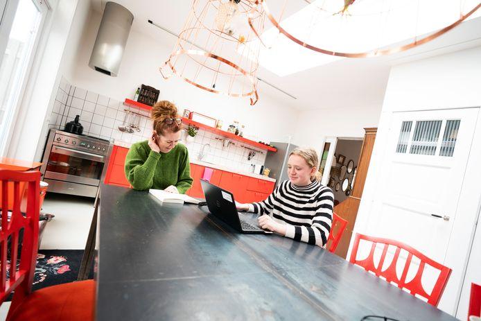 Monica Esko en haar dochter aan de keukentafel.