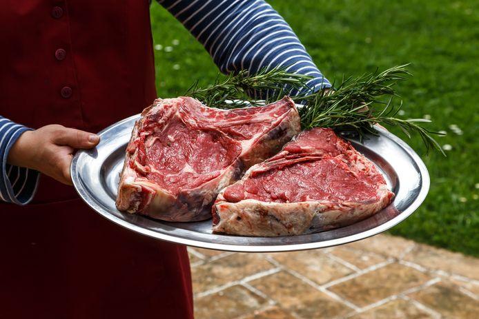 Een vrouw met twee grote steaks.
