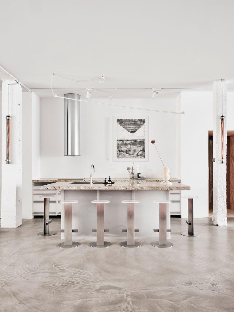 In de keuken combineerde Sabine een granieten keukenblad met kastdeurtjes van transparant acryl,en krukken en een dampkap in roestvrij staal.   Beeld Christoffer Regild/Living Inside.