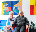 Viktor Majdandžić met zijn vrouw Pieneke in de huiskamer die volhangt met kleurige schilderijen