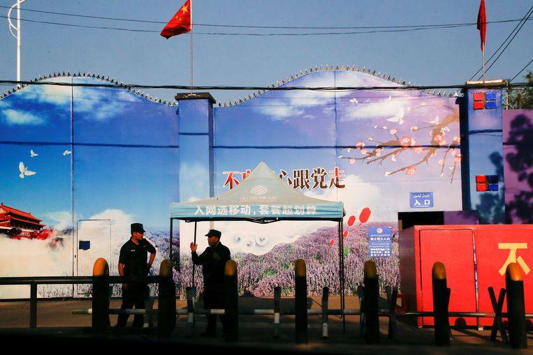 Beveiligers staan aan de poorten van wat officieel bekend staat als een centrum voor beroepsonderwijs in Huocheng County in de autonome regio Xinjiang Uighur, China Beeld REUTERS