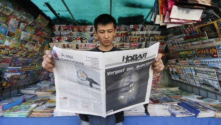 Een inwoner in Moskou leest een uitgave van Novaja Gazeta die is uitgebracht na de ramp met vlucht MH17. De tekst op de voorpagina luidt: 'Vergeef ons, Nederland'. Beeld EPA