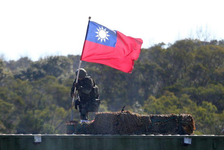 Een soldaat houdt een Taiwanese vlag omhoog tijdens een militaire oefening in Hsinchu. Beeld AP