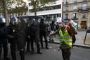 Een demonstrant met een geel hesje staat oog in oog met de politie tijdens de demonstratie in Parijs. (28/08/2021)