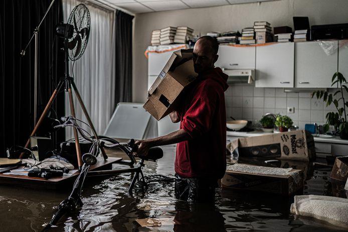 Een inwoner van Meerssen in zijn ondergelopen woning.