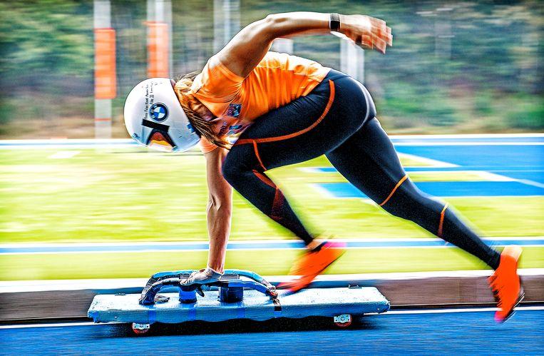 Kimberley Bos tijdens een training op de schuine helling op de atletiekbaan op Papendal met haar zelf gebouwde plank op wieltjes als vervanging van de skeleton.  Beeld Klaas Jan van der Weij / de Volkskrant