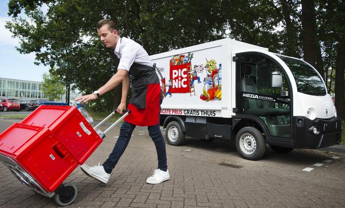 Een medewerker van de online supermarkt Picnic bezorgt boodschappen bij een klant