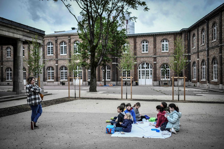 Kinderen van ouders die in de zorg werken lunchen bij de privéschool Eugene Napoleon Saint-Pierre Fourier. Beeld AFP