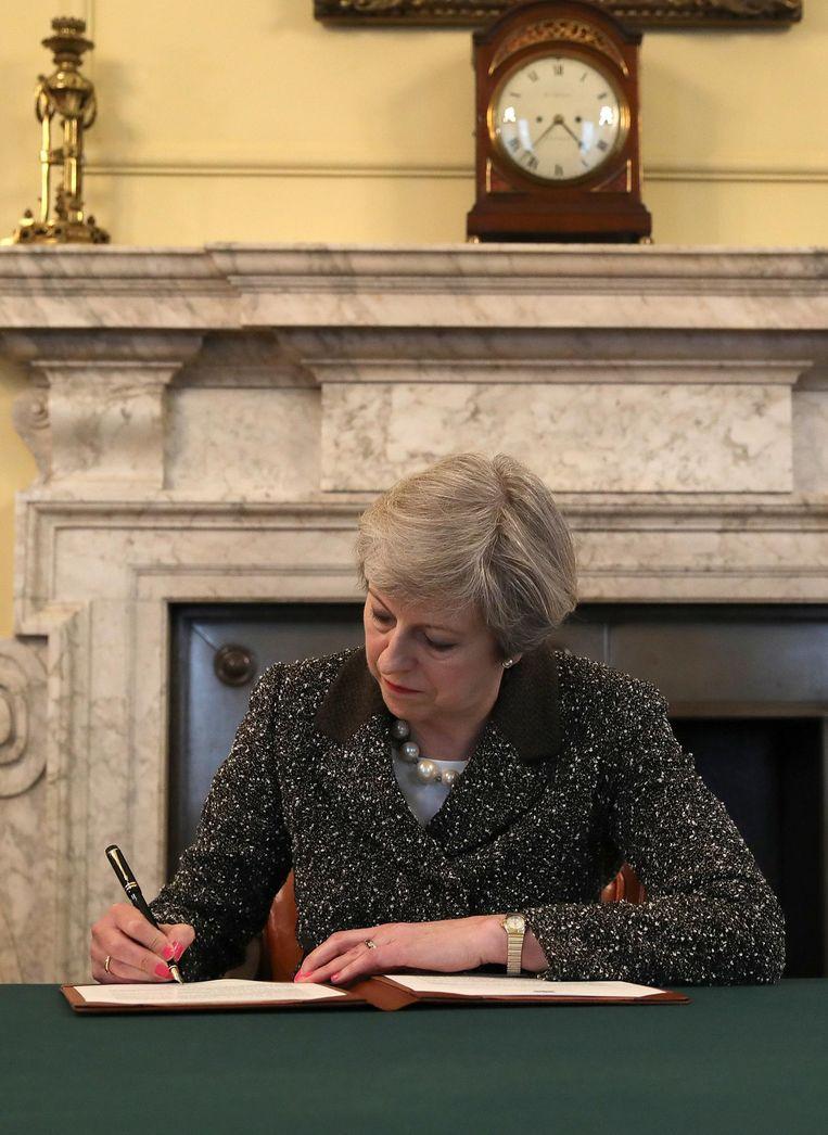 Theresa May zet haar handtekening onder de artikel-50-brief. Beeld REUTERS