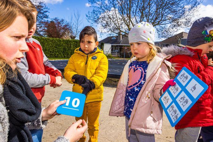 Groep 1-2 van De Dromenvanger in Oudheusden krijgt rekenbingo op Nationale Buitenlesdag. Hannah stelt een vraag aan juf Marit over de bingokaart.
