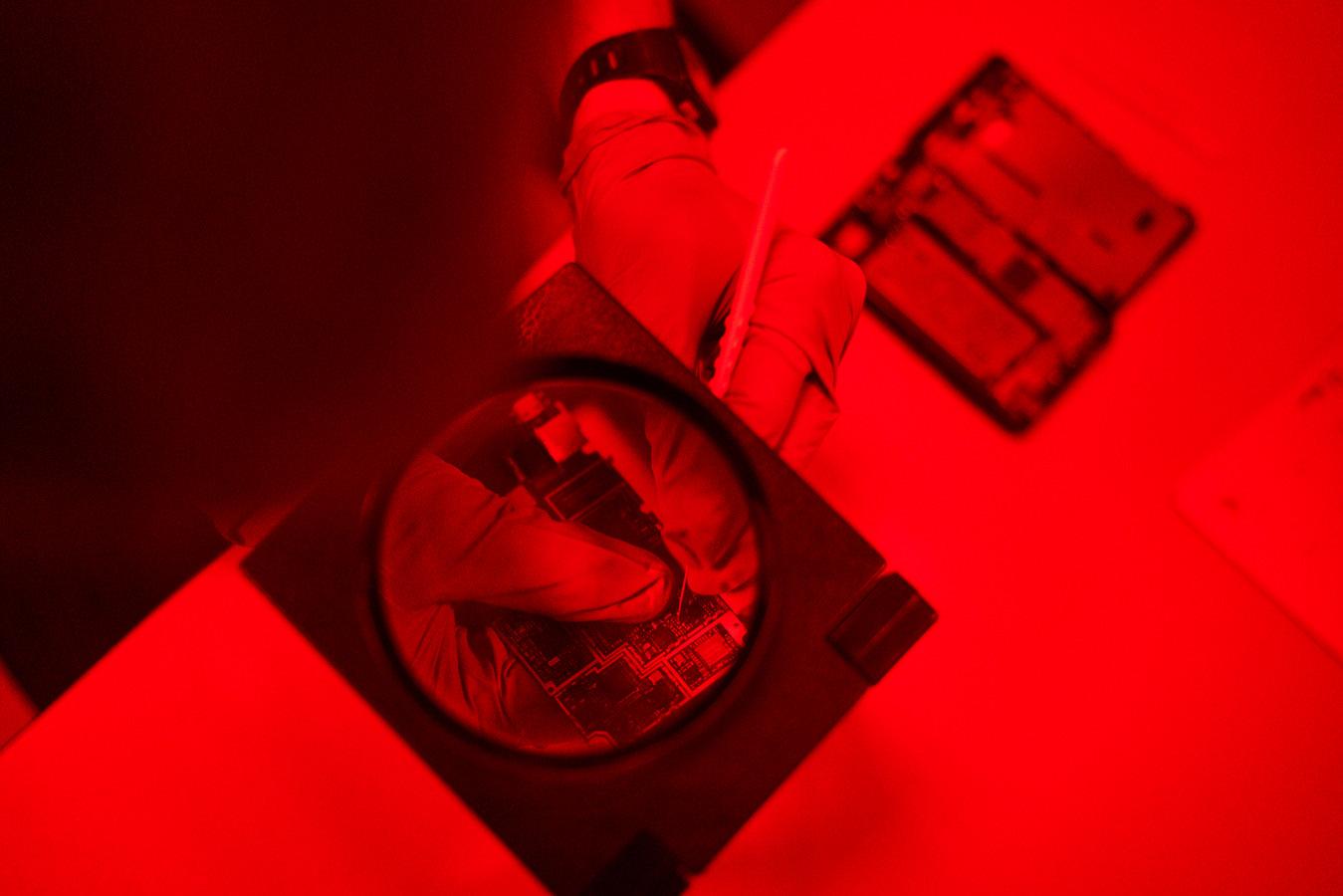 Een onderzoeker van SCK CEN werkt aan de weerstanden van een smartphone in een fotokamer.