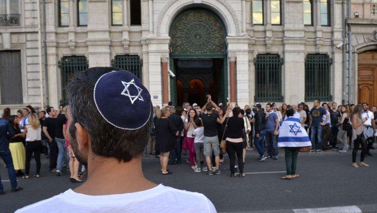 Een man met een keppeltje op tijdens een protest voor een synagoge in Frankrijk. Beeld afp