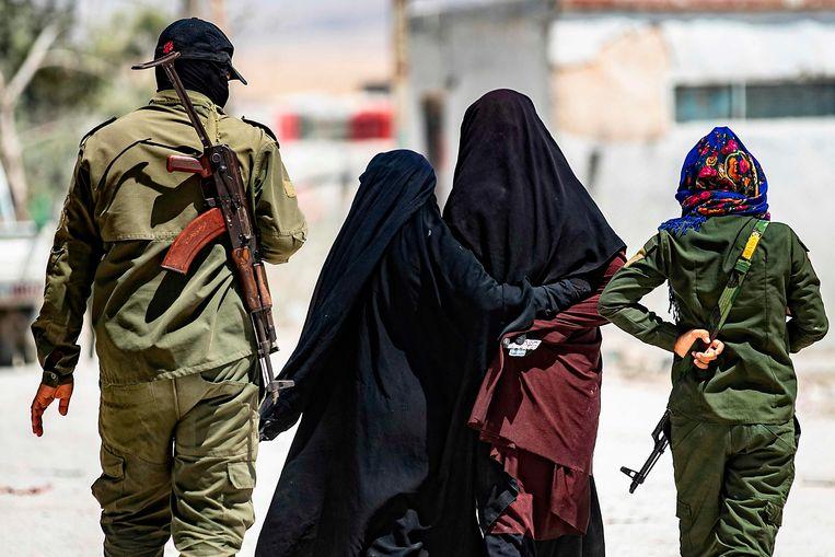Koerdische bewakers escorteren twee IS-vrouwen in kamp al-Hol in het noordoosten van Syrië. De foto is genomen op 23 juli 2019, voordat de Turkse invasie in Noord-Syrië plaatsvond.  Beeld AFP