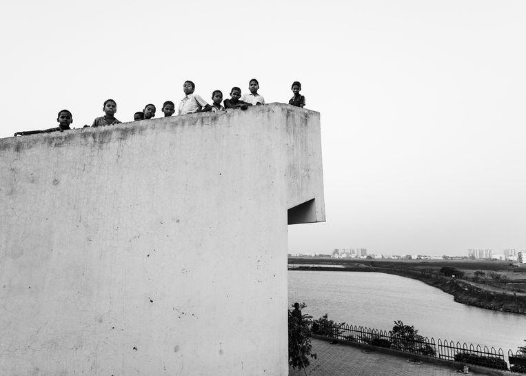 Graduation 2017 Manu De Caluwe  Tribe Done Gone  Een Indische NGO in Bhubaneswar interneren 25000 kinderen uit inheemse stammen. Het zijn de laatste 62 originele stammen uit de provincie Odisha. Toerisme is er zeer ongewoon. Door de afname van de bossen en het levensonderhoud hebben deze kinderen steeds minder kans om sterk op te groeien. Deze generatie wordt eveneens gebruikt en toegeëigend door organisaties en personen die hier munt willen slaan of roem te winnen. De stammen zijn naïef tegenover de wereld van vandaag. Enerzijds krijgen de kinderen educatie, onderdak, voeding en medicatie maar aan de andere zijde van de medaille is er een enorm winstbejag door deze 25000 jongeren hun inheemse kunst te laten nabootsen wat op de markt kan verkocht worden. Rijke CEO's, politiekers en beroemdheden maken er gebruik van om bijvoorbeeld knielend voor een groepje van deze inheemse kinderen te poseren voor de foto die hun imago zal opkrikken. Eveneens verliest de nieuwe generatie een groot deel van zijn eigenheid door de betrokkenheid van onze moderne wereld. Stilletjes aan doven de stammen uit. In deze reeks toon ik het beeld waarin er geen onderscheid meer valt te maken tussen de kinderen van de verschillende stammen. Daaruit haal ik een vijftal portretten waarin meer eigenheid valt te aanschouwen en ook vervoeg ik ze met een vijftal zwart-wit beelden die hun leven in het instituut laten zien wanneer ze op zichzelf buiten rondlopen. Tussen goede en slechte intenties is het niet steeds duidelijk wat het beste is voor de kinderen. De wereld heeft hen ingehaald en er is nauwelijks plaats voor het verleden. Beeld Manu De Caluwe