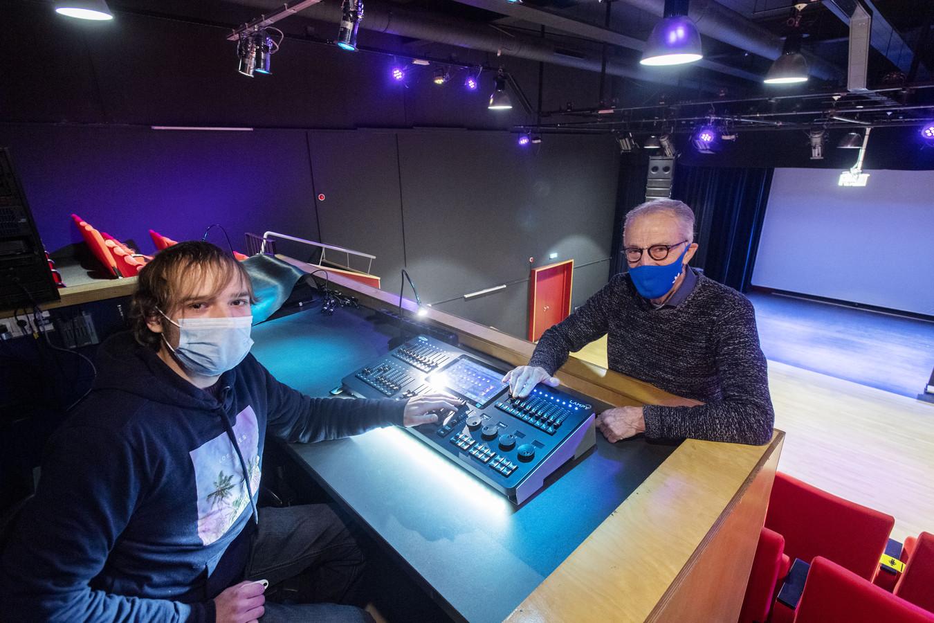 Henk Hogebrug (77, rechts) werkt met collega-vrijwilliger Donolan de Oliveira Soares aan de theatertechniek van het Kulturhus.  De verlichting is zojuist gemoderniseerd, nu het geluid nog.