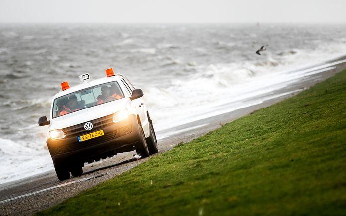 Een auto van Wetterskip Fryslân op een dijk bij Lauwersoog.