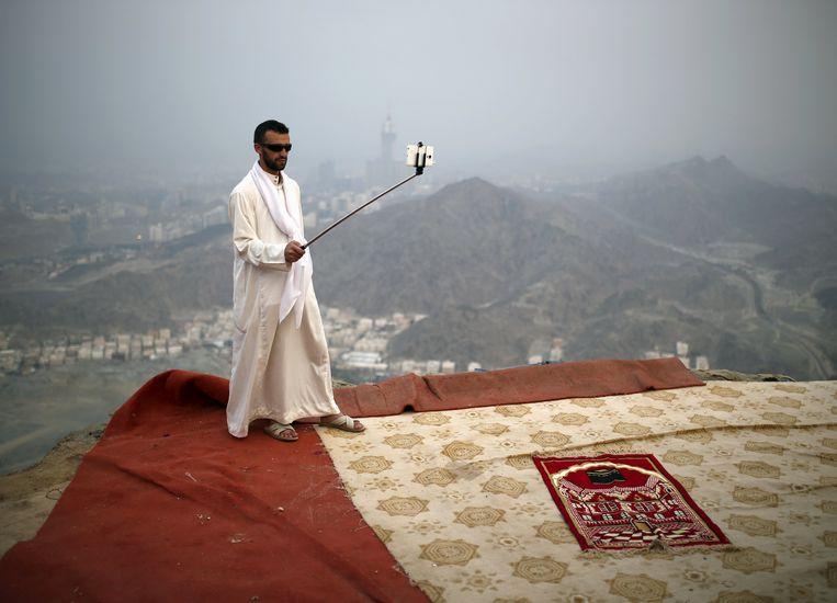 Een moslimpelgrim neemt een selfie bovenaan de berg Ghar Thor, bij Mekka. Beeld REUTERS