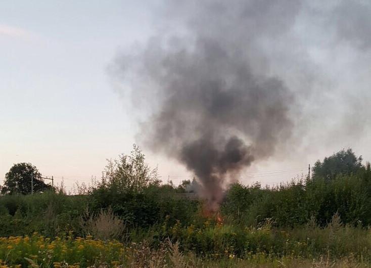Restanten van de brandende vluchtwagen nabij het spoor.