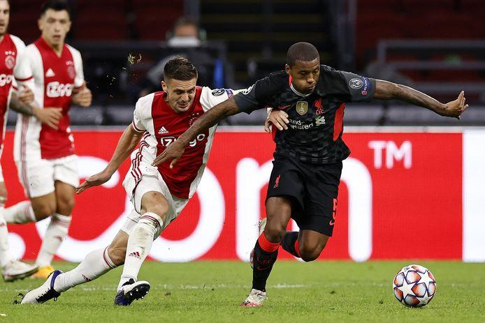 Liverpool-middenvelder Georginio Wijnaldum op het 'te modderige' veld in de Johan Cruijff Arena in duel met Ajacied Dusan Tadic.