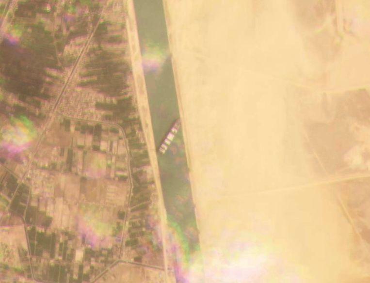 Satellietbeeld van de Ever Given, die overdwars ligt tussen de twee kades van het Suezkanaal. Beeld AP