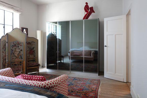 De rode kleur van de Engelse sofa herhaalt zich in het tapijt, de paravent, de sierkussens en de sculptuur die boven op de jarenzeventigkast staat.