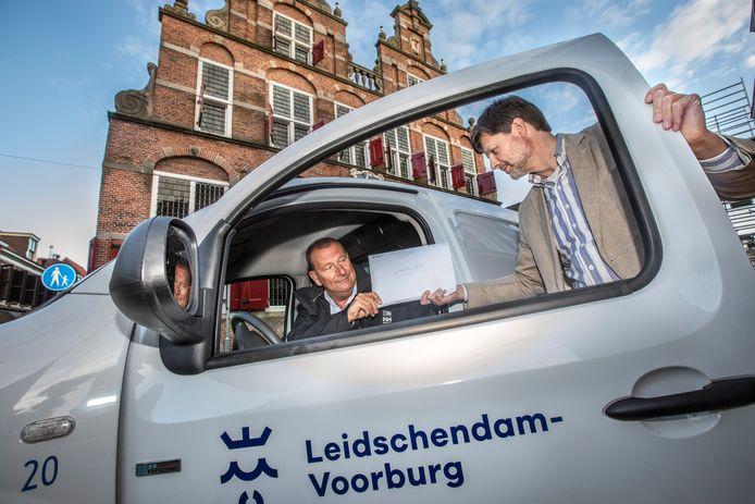 Bode Jan van Rijn neemt voor het stadhuis de enveloppe met stembriefjes in ontvangst van griffiemedewerker Edgar de Bruin.