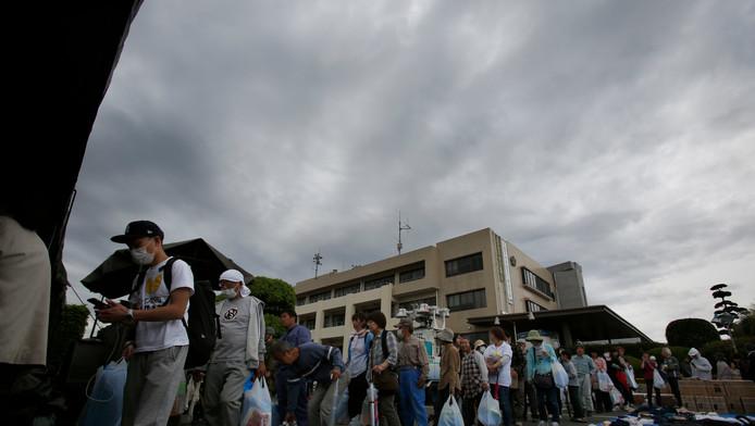 Inwoners van Mashiki wachten bij een distributiecentrum op voedsel.