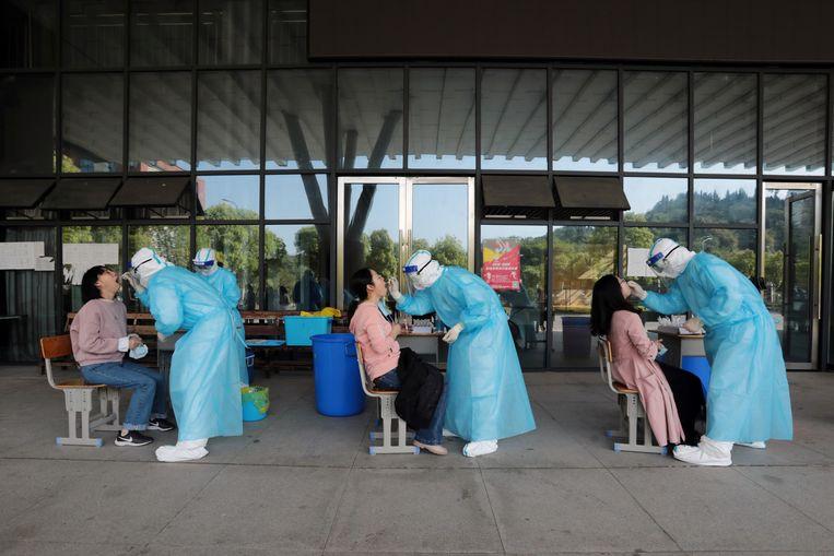 Verpleegkundigen nemen speekselmonsters van middelbare schoolleraren in Yichang, China.  Beeld REUTERS