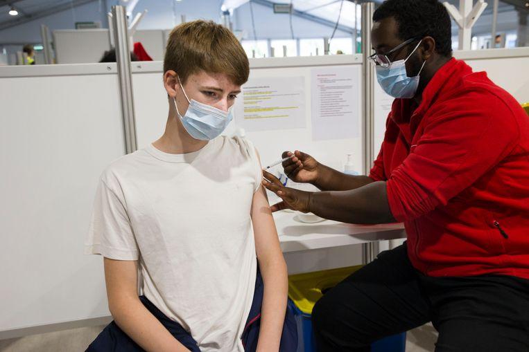Tiener Sam, vijftien jaar, krijgt zijn vaccinatie in Poortugaal. Hij krijgt een enkele vaccinatie met Pfizer omdat hij al corona heeft gehad.  Beeld Arie Kievit