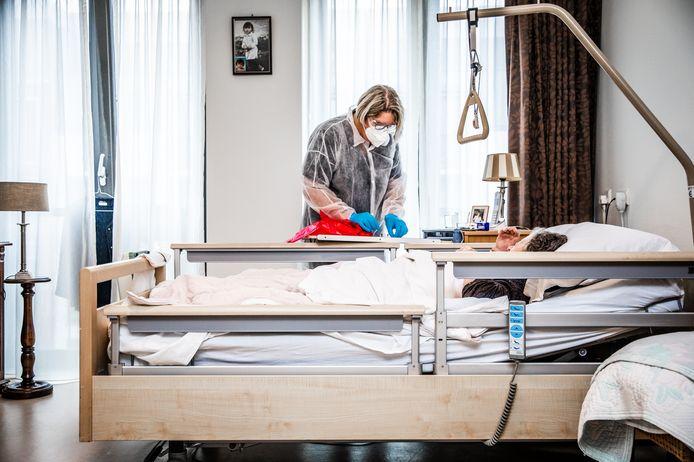 Een verpleegster van een verzorgingshuis verpleegt een coronapatiënt. Een foto ter illustratie.