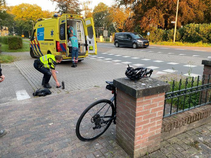 Een politieagent raapt onderdelen op van de fiets die door een busje is aangereden. De fietser wordt in de ambulance getild voor verdere behandeling in het ziekenhuis.