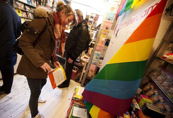 Bij Gay & Lesbian Boekhandel Vrolijk in Amsterdam deelt de homobelangenorganisatie COC regenboogvlaggen uit aan klanten. Die zijn bedoeld voor het protest tijdens het bezoek van Poetin maandag.