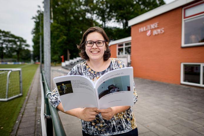 Evelien Jansen langs de lijn bij Hulzense Boys met de gedichtenbundel van haar overleden vader, die bij de jarige club als Gait van de Venneboer letterlijk geschiedenis schreef.