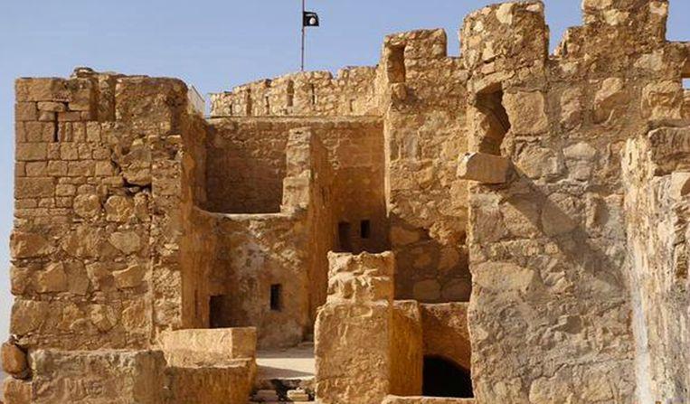 Een IS-vlag op de top van de oude citadel in Palmyra. Beeld ap