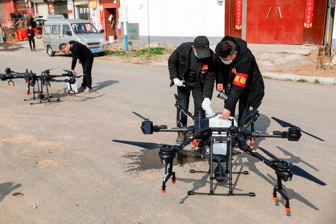 Drones worden verder ook ingezet om ontsmettingsmiddel rond te sprayen. Hier vullen locals uit Pingdingshan een drone met een desinfectiemiddel om het daarna boven hun dorp te verstuiven.