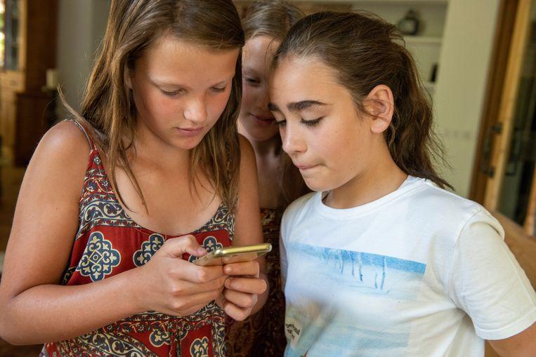 Meisjes bekijken filmpjes op de populaire app TikTok. Beeld Patricia Rehe, Hollandse Hoogte