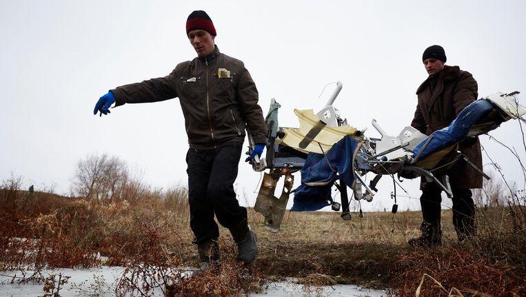 Vrijwilligers uit Grabovo zoeken in het rampgebied naar de overgebleven kleine wrakstukken en persoonlijke bezittingen van de MH17 vlucht. Beeld anp