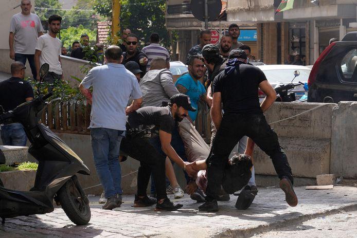 Des partisans d'un groupe chiite allié au Hezbollah aident un camarade blessé au cours d'affrontements armés qui ont éclaté lors d'une manifestation dans la banlieue sud de Beyrouth, à Dahiyeh, au Liban, jeudi 14 octobre 2021.